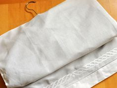 Transforme fronhas antigas em sacos de roupa para manter suas roupas fora de época parecendo novas.