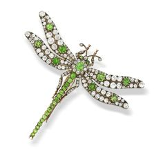 An early 20th century demantoid garnet and diamond dragonfly brooch  Mounted en tremblant, the thorax set with an oval-cut demantoid and old brilliant-cut diamond cluster, the abdomen with a graduated row of circular-cut demantoid garnets, to wings finely pierced and set with old brilliant, rose and cushion-shaped diamonds, highlighted with oval and circular-cut demantoid garnets, mounted in silver and gold, diamonds approximately 2.90 carats total, one demantoid and one diamond deficient.
