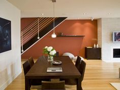 The continuity of the dark cabinetry, stair mass and simple lines of the furnishings against the natural wide plank flooring and the burnt orange accent wall beyond create a memorable setting in this Washington DC Duplex. Artwork by AndreasCharalambous.com