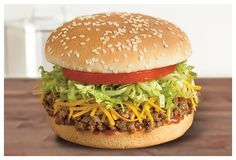 "The California-based taco chain Del Taco is celebrating its anniversary by serving a ""Bun Taco."" It's basically what would normally go inside a taco (seasoned beef, cheddar cheese, lettuce, and tomato) but it all gets crammed inside a sesame seed bun. Taco Johns Taco Burger Recipe, Taco Burger Recipe Ground Beef, Ground Beef Tacos, Ground Beef Recipes, Del Taco, Hamburgers, Mexican Food Recipes, Gourmet Recipes, Gourmet Foods"