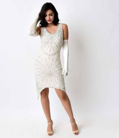 Vamp up your vintage, gals! Presenting The Caulfield, a striking reproduction flapper that mesmerizes in ivory mesh, crafted in a jazz age inspired 1920s silhouette with a modern twist that's available only at Unique Vintage! A sleeveless, scalloped v-bod
