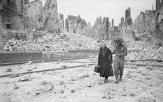 A British soldier escorts a civilian in Caen, July 1944