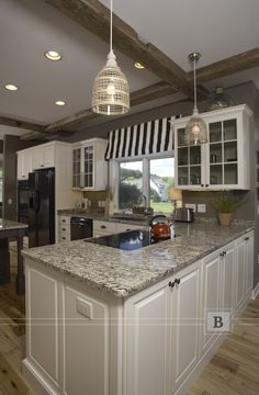 Painted cabinetry with glass doors, wood beams and country kitchen flare create this warm and inviting space.