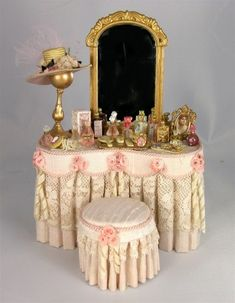 This lovely ladies vanity is draped in pale pink silk fabric, with an antique lace overlay. Rope cording outlines the scalloped apron which is accented with silk roses and ribbon bows. Miniature Dollhouse Furniture, Miniature Houses, Diy Dollhouse, Miniature Dolls, Dollhouse Miniatures, Victorian Dolls, Victorian Dollhouse, Doll House Crafts, Doll Houses