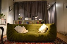 Love the #Togo sofa from Ligne Roset in this olive green! Made even better by the #265 Flos light