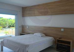 A suíte master conta com painéis em madeira cerejeira atrás da cama feitos sob medida para o ambiente.