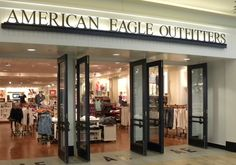 """American Eagle Outfitters: """"Beach house"""" store design used from 2000 - 2012. Earlier buildout. San-serif pairings of """"AE"""" letters inlaid into polished concrete floor outside each set of double doors."""