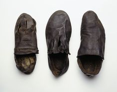 Full image caption Selection of medieval shoes. The shoe on the left is a woman's welt construction shoe for the left foot with a narrow oval toe, and narrow waisted sole which shows signs of outdoor wear. The high cut vamp has a straight edge, and the decoration consists of three longtitudinal cuts from the toe with two rows oblique slashes along the edge of the throat. The other two shoes are of leather and plain in design.   Date 1570 AD - 1600 AD