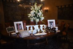 Sign in table features pictures of the bride and groom with a large white floral arrangement   One Fine Day Photography   villasiena.cc