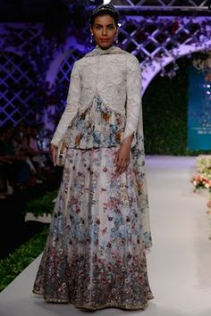 Varun Bahl indian designer runway couture 2016 collection online an ivory net skirt with pink and blue floral print highlighted with sequins and beads. It has a gold running cutdana border. It comes along with an ivory beads and stones studded scaled cotton jacket blouse with a paneled floral printed georgette lining.Shop now on www.carmaonlineshop.com #ICW2016 #VarunBahl #carmaonline #couture #romantic #floral #lehenga #embroidery #designer #delhi #wedding #whimsical #shoponline