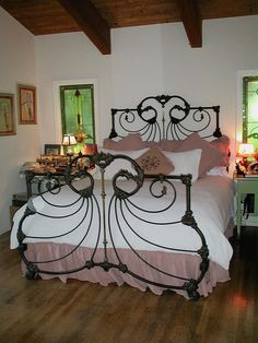 This French Curve side antique iron bed has been flawlessly converted to a modern king size.