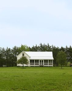 An 1850s guesthouse sits across the meadow from the main house on this 180-acre farm in Round Top, Texas.