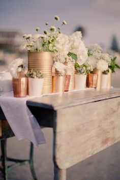 Kleur conservenblikken met spuitlak en plaats er verschillende bloemen in voor sfeervolle en feestelijke decoratie.