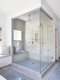 Spacious Setup - shower Multifeature Shower A glass steam shower fills one corner of the bathroom. Built-in benches and a two-shelf niche cut into the limestone-lined wall make the shower setup convenient and relaxing. The shower connects to the rest of the bath with a similar floor tile treatment.