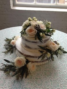 2 tiered naked cakes topped with blush open cut roses, seeded eucalyptus and gray berries. Cake designed by Flowers by the Bunch
