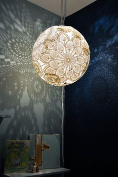Doily Light made from doilies, Elmers glue, and an IKEA light kit for about 10 dollars complete. Sends a great image on to wall and looks great when turned off. Holds up well if glue is allowed to dry completely.