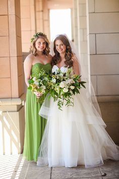 the bride and her bridesmaid hold their loose and unstructured bouquets of white roses, white larkspur, white ranunculus,white stock, white parrot tulips, white majolik spray rose, tuberose, white lisianthus,jasmine trails, bay leaf and magnolia leaf.