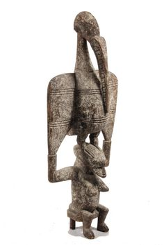 Africa | Sculpture of Hornbill Supported by Seated Human Figure from the Senufo people of the Ivory Coast | Wood, paint | 20th century