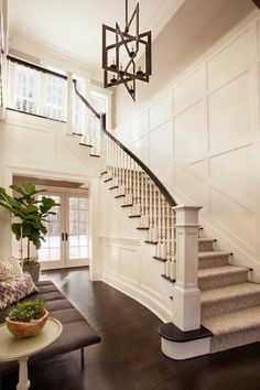 Carpeted stairs and a unique chandelier grace this narrow shotgun-style foyer. The foyer leads upstairs, to the left, and even through to the backyard. Foyer Staircase, Entry Stairs, Curved Staircase, Entry Hallway, Staircase Design, Staircases, Entrance Hall, Flur Design, House Tours