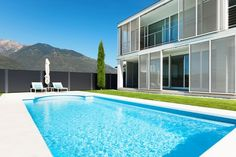The above beautiful glistening pool belongs to a modern contemporary house with full height sliding shade screens and a small balcony. A mountain backdrop provides a quiet serene and majestic feel Pool Komplettset, Swimming Pools, Skimmer Pool, Shade Screen, Modern Contemporary Homes, Construction, Good Company, Backdrops, Luxury