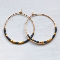 These earrings were created by hand in London.The earrings are a noticable size at 30mm in diameter and are adorned in a very edgy yet elegant way, using fair trade faceted 22 carat gold vermeil beeds along with dark grey glass beads. They can be worn day and night and look fab with layered black as well as monocrome beige/white. They would make a great gift for any woman who likes to dress to impress - yourself included!The earrings come in a velvet pouch safely placed in m...