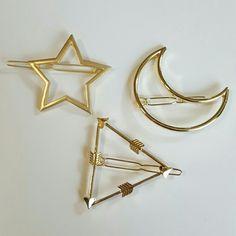 """3 Hair Barettes This listing is for a bundle of three brand new and unused gold tone hair pin barrettes. The first is a star that is 2"""" across the second is a cresent moon shape and is 2 1/4"""" across and 1"""" wide. The third is three bows arrows are lined into a triangle and each one is 2"""" long. Great with your favorite shirt and jeans. Other great hair accessories in my closet. Accessories Hair Accessories"""