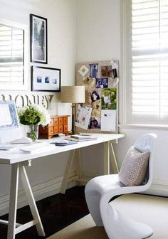"A shapely Panton chair and all-white palette define this cozy-chic space.    ""This home office has all the essentials—an inspiration board, pretty but functional furniture, a desk with plenty of surface area, favorite works of art, and homey comforts like a pillow, flowers, and a lamp,"" says Ashley White, creator of the popular blog, Decorology."
