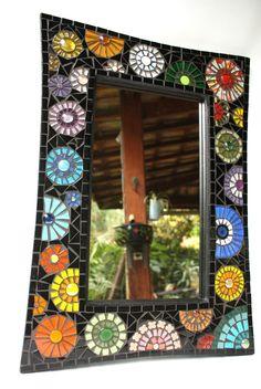 Uma explosão de alegria! É esse o sentimento que temos ao nos deparar com essa moldura em mosaico com flores super coloridas que realçam ainda mais com o fundo escuro.  A diversidade de cores, formas e materiais que compõem essa moldura de espelho certamente trará ao seu ambiente alegria e muita ...