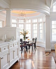 Round breakfast nook filled with windows and just off an all-white kitchen.