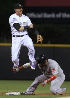 Colorado Rockies shortstop Troy Tulowitzki, top, watches his throw to first after forcing out Boston Red Sox's Shane Victorino at second bas...