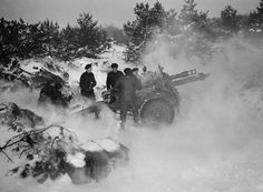 "Gunners of ""B"" Troop, 5th Battery, 5th Field Regiment, Royal Canadian Artillery, firing a 25-pounder (11.4 kg) gun. Malden, Netherlands, February 1st 1945.  (L-R): Sergeant Jack Brown, Bombardier Joe Wilson, Gunners Lyle Ludwig, Bill Budd, George Spence and Bill ""Scotty"" Stewart. Photograph by Lieutenant Michael M. Dean."