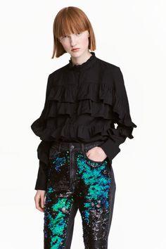 Bluzka z falbanami: Bluzka z miękkiej tkaniny wiskozowej z długim rękawem. Falbanka wokół szyi, karczek, zapięcie na guziki, ozdobne falbany z przodu. Szeroki fason i nieco dłuższy tył.