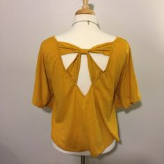 Yellow circle shirt with cutout back This shirt is super cute for many occasions, and it has an adorable bow back. Delia's Tops Blouses