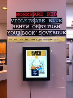 "Valentine's poem : overdue reminder : February display : ""Roses are red, violets are blue, renew or return, your book's overdue"" (@ MEI Secondary Library) : above digital frame that scrolls through overdue lists"