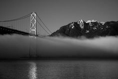 Lions Gate Bridge mist with mountains in the background.
