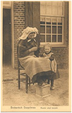 """Darning socks outside in the yard, with feet on a foot warmer, with a small child next #Brabant"""