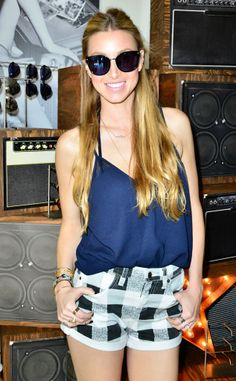 Whitney Port shows off her legs at Coachella in a pair of plaid shorts, completing the look with a tucked in tank.