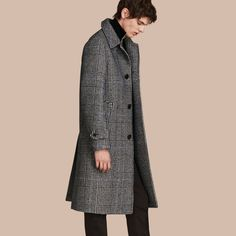 A technical Burberry wool coat in a Prince of Wales check, cut with sharp details for smart dressing.