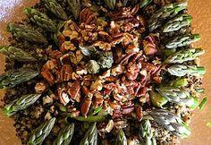 Salade d'asperges crues sur un lit de quinoa et couverte de pacanes grillées.