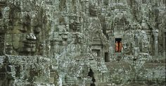 Monges budistas parados à porta nas ruínas do Templo de Bayon, em Angkor Wat, no Camboja