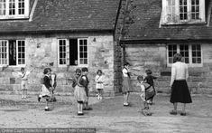 School children playing games in the playground at primary school. Love the knee-high socks! We wonder why the girl at the window can't go out to play? Crawley Down, Children At The School Old Post Office, Nostalgic Images, English Village, Back In Time, Private School, British History, School Days, Historical Photos, Country Life