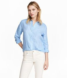 Blue. Longer, straight-cut shirt in woven linen fabric. Turn-down collar, buttons at front, long sleeves with buttons at cuffs, and rounded hem with slits