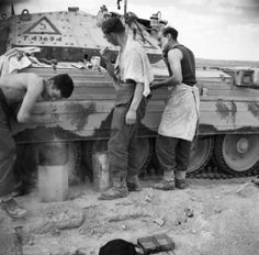 The crew of a Crusader tank have a wash and shave by the side of their vehicle, March 1942. Note the roughly applied camouflage paint on the...