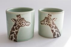"Madesmith exclusive. 2 ceramic cups with an original illustration of a giraffe by Susannah. Celadon glaze. Approximately 3.5"" tall, 3"" at rim, 10oz. Each SKT Ceramics piece is individually crafted out"