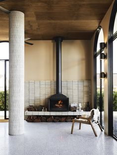 creative fireplace design at the blacksmith provedore restaurant. the fireplace sits center stage to create a sense of homeliness. get this look with our terracotta subway tiles, such as our architect's palette or our bejmat zellige tiles. Interior Design Studio, Home Interior, Interior Architecture, Interior Cladding, Century Hotel, Mid Century, Walnut Timber, Freestanding Fireplace, Timber Beams