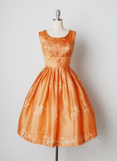 Vintage 1950s soft orange silk sleeveless dress. Front bodice pleated detail with fitted waist and full pleated skirt. Decorative front buttons with