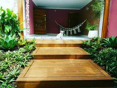 Um lindo deck de madeira com jardim de bromelia ao lado direito e esquerdo