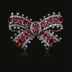 RUBY AND DIAMOND BOW BROOCH, MID 19TH CENTURY Designed as a ribbon tied bow set with graduated lines of oval rubies mounted in cut-down collets bordered with lines of old-mine and circular-cut diamonds. From the Estate of Christian, Lady Hesketh, sold by Sotheby's.