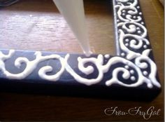 Put glue on a cheap frame in a design then paint over when dry. Looks like a hand carved frame! Awesome DIY!