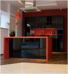 This eye-catching custom made display has black low iron painted glass door fronts. The units have an aluminum frame and black interiors. The red box shelf is in a red high gloss lacquer with four halogen lights. All drawers on the island unit have a soft close mechanism. The worktop is 50mm Eros Stellar red quartz - with sparkly bits! retails from £15000
